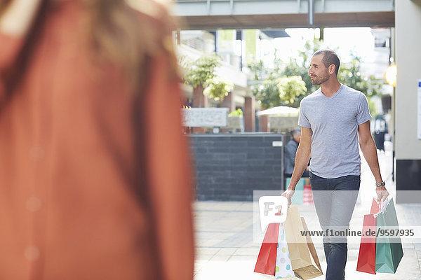 Mittlerer erwachsener Mann mit Einkaufstaschen  der hinter einer Frau hergeht.