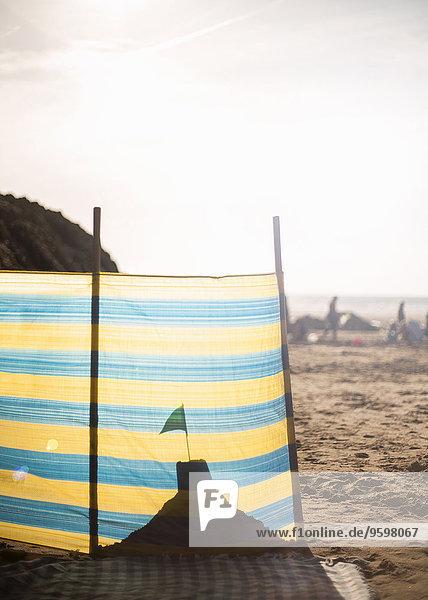 Sandburg hinter Windschutz am Strand