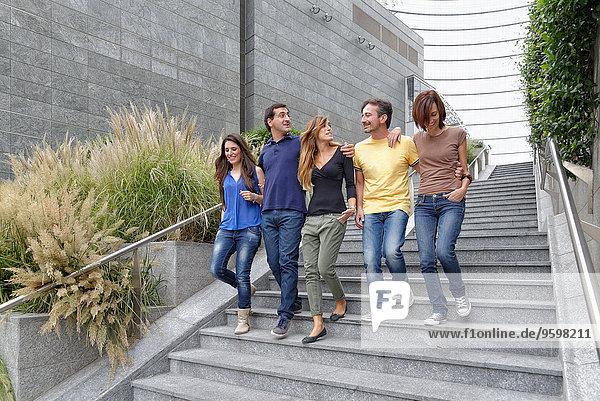 Gruppe von Freunden  die gemeinsam die Treppe hinuntergehen
