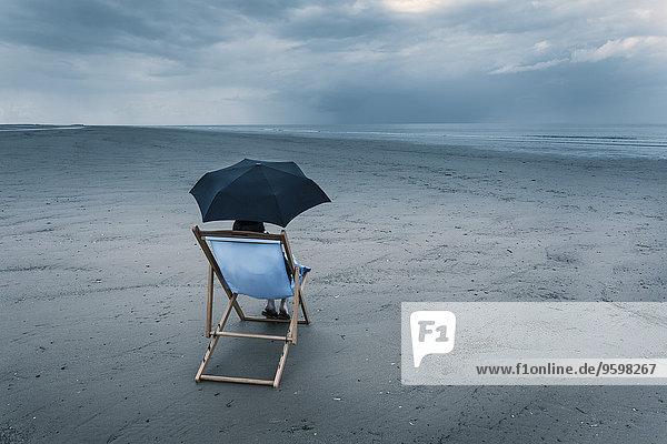 reife Frau sitzt auf Liegestuhl am stürmischen Strand  unter dem Regenschirm