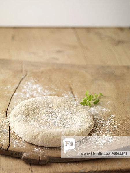 Pizzateig auf Schneidebrett mit Mehl bestreut