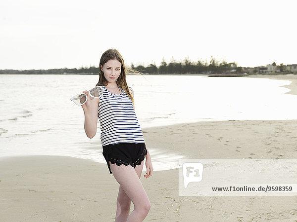 Junge Frau mit übergroßer Sonnenbrille am Strand