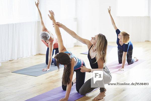 Frauen knien und Arme heben in der Pilates-Klasse