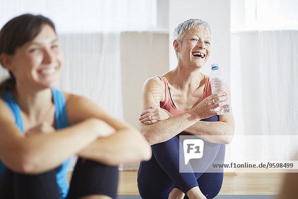 Two women taking a break in pilates class
