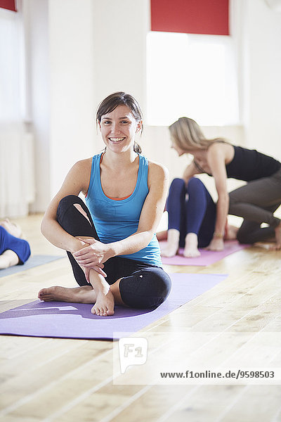 Portrait of young woman sitting on floor in pilates class