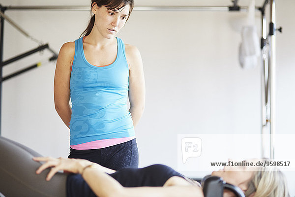 Mature female student lying on trapeze table in pilates gym