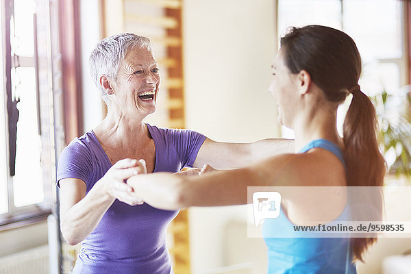 Young female student laughing with teacher in pilates gym