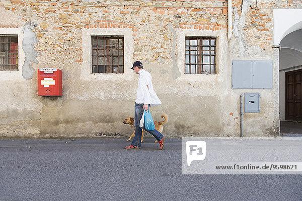 Mann gehender Hund auf der Straße  Suno  Novara  Italien