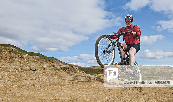 Mountain bikers cycling through Reykjadalur valley  South West Iceland