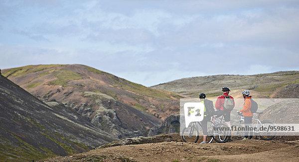 Drei Mountainbiker machen eine Pause am Aussichtspunkt  Reykjadalur-Tal  Südwest-Island
