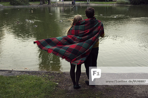 Rear view of young couple wrapped in blanket on park lakeside