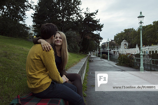 Young couple sitting face to face on park wall