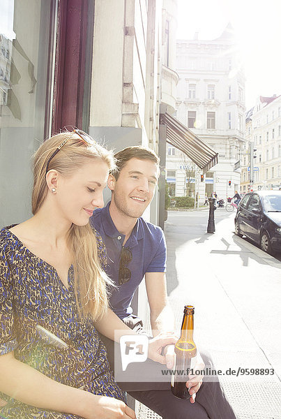 Young couple at sidewalk cafe drinking beer