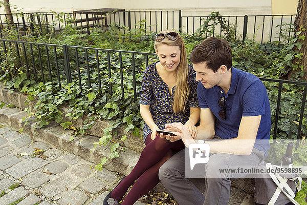 Junges Paar auf der Wand sitzend mit Blick auf das Smartphone