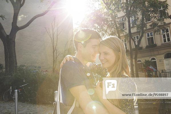 Young couple hugging on suburban street