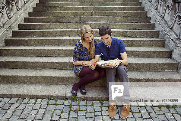 Young couple sitting on old street stairway reading newspaper