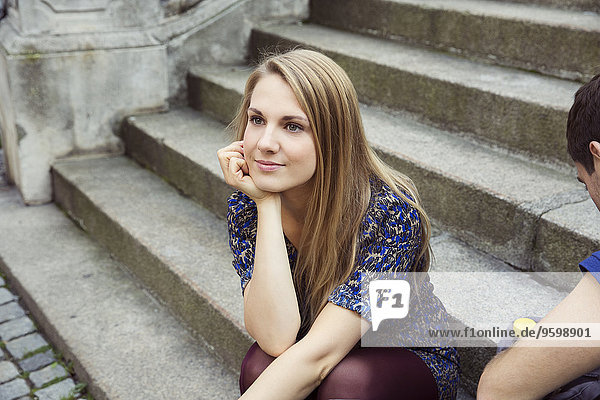 Young woman sitting on old street stairway daydreaming