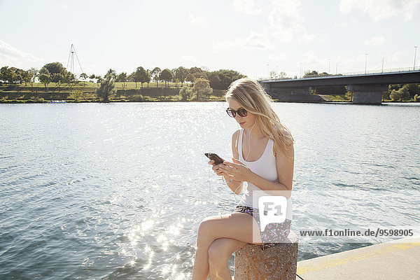 Young woman sitting at riverside texting on smartphone  Danube Island  Vienna  Austria