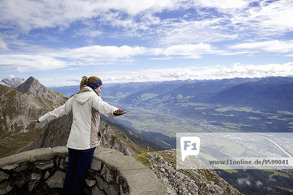 Young woman with arms open on top of mountain  Innsbruck Tyrol  Austria