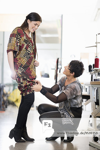 Mature seamstress adjusting length of customers dress in workshop