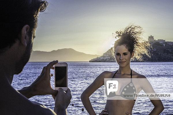 Mann fotografiert junge Frau im Urlaub