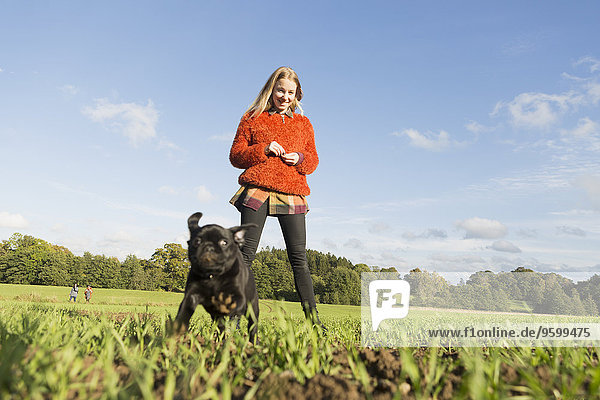Happy young woman with puppy on field