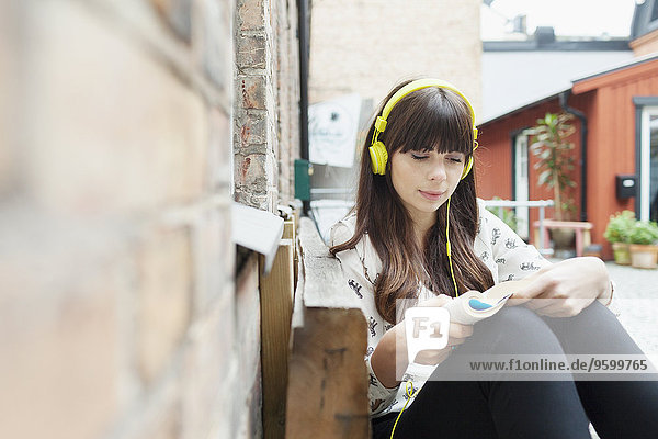 Young woman listening music while reading book at cafe backyard