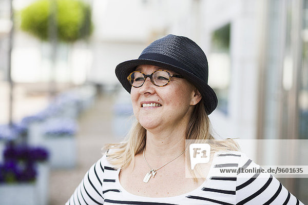 Happy mature woman wearing glasses and hat outdoors