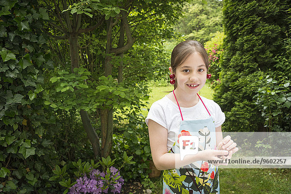 Girl in garden  cherries dangling from her ears