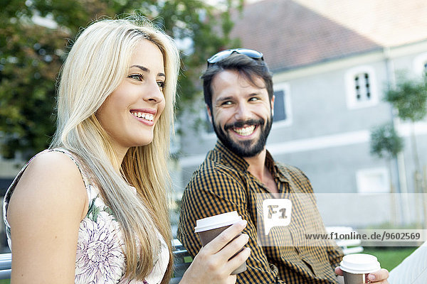 Happy young couple with disposable cups in hands