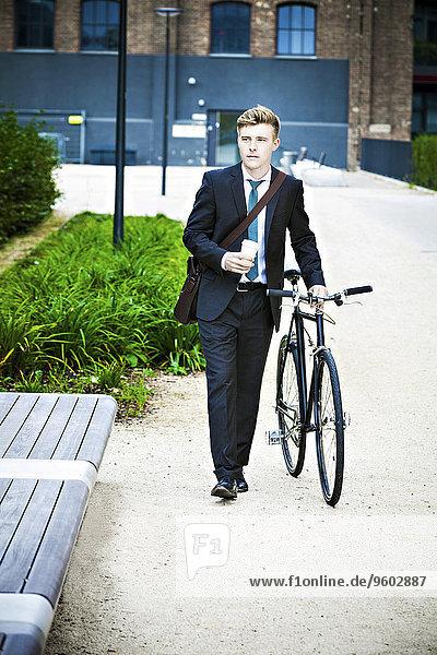 Geschäftsmann schieben jung Fahrrad Rad
