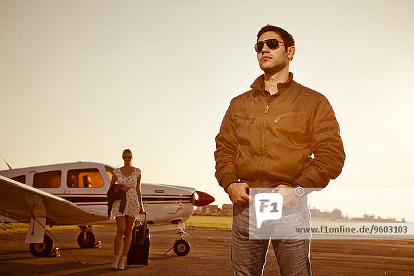 Flugzeug stehend Mann frontal Propeller Frau im Hintergrund