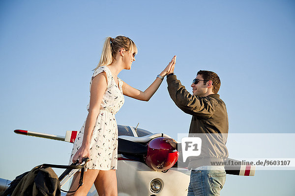 Couple giving each other high-five in front of private airplane