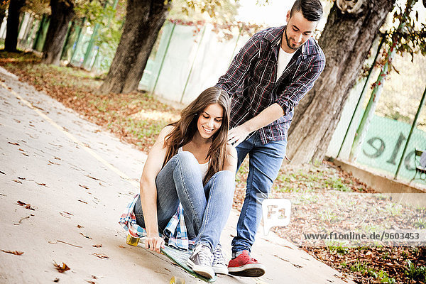 Young woman skateboarding  man supporting her