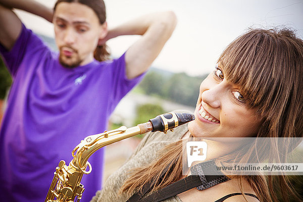 Young woman with saxophone  boyfriend in background