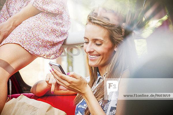junge Frau junge Frauen benutzen sitzend Sitzmöbel Auto Smartphone Sitzplatz