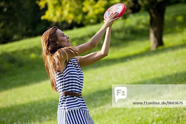 Außenaufnahme junge Frau junge Frauen Frisbee freie Natur spielen