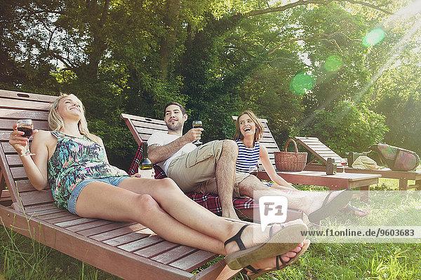 Mensch Entspannung Menschen Rotwein jung trinken Liege Liegen Liegestuhl