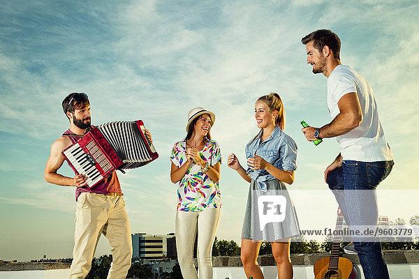 Dach Mann Freundschaft Party tanzen Akkordeon spielen
