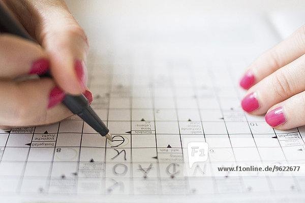 Frau macht Kreuzworträtsel