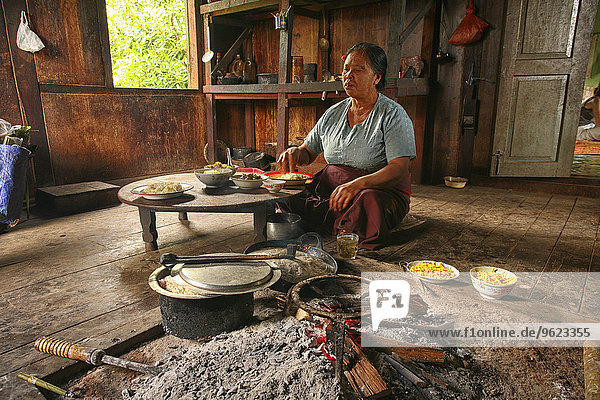 Myanmar  Kalaw  woman cooking at fireplace