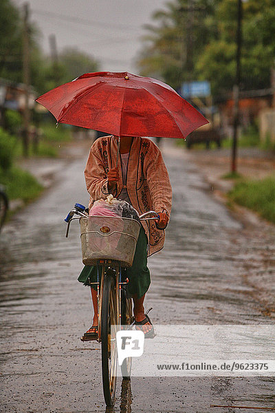 Myanmar  woman on bike in monsoon rainfall
