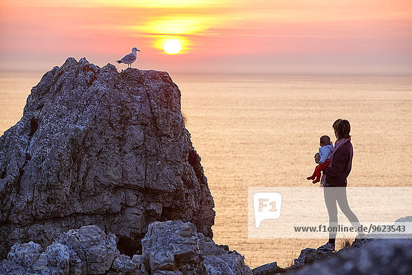 France  Brittany  Pointe de Pen-Hir  Woman with child watching sunset