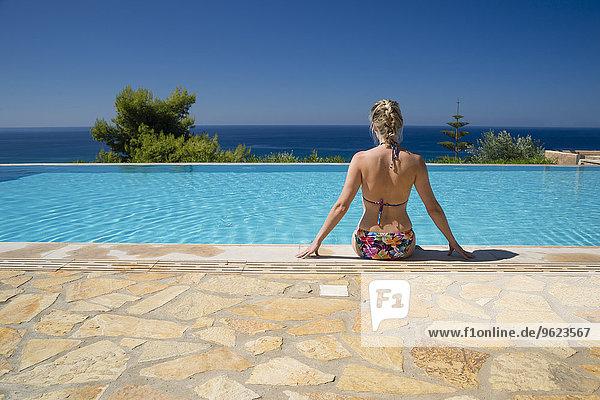 Griechenland  Peloponnes  Frau am Poolrand mit Blick aufs Meer