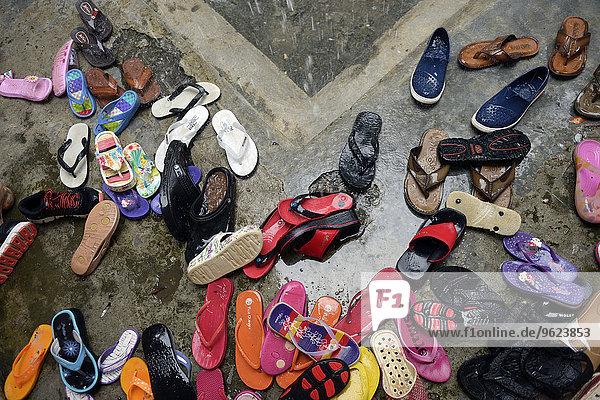 Indonesien  Aceh  Gampong Nusa  Schuhe im Regen vor einem Gemeindezentrum
