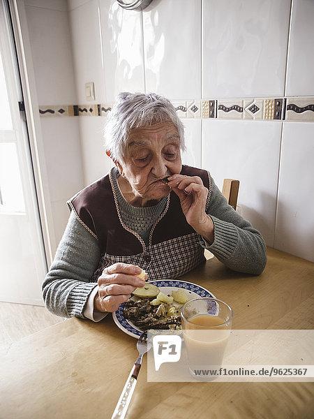 Alte Frau isst Fisch und Kartoffeln in der Küche
