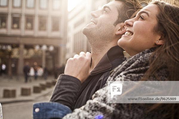 Deutschland  Köln  lächelndes junges Paar  das aufschaut Deutschland, Köln, lächelndes junges Paar, das aufschaut