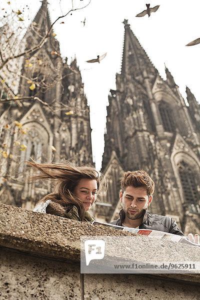 Deutschland  Köln  junges Paar beim Betrachten des Stadtplans vor dem Kölner Dom Deutschland, Köln, junges Paar beim Betrachten des Stadtplans vor dem Kölner Dom