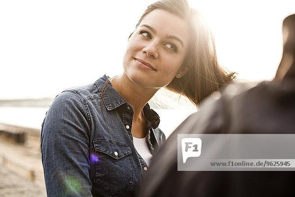 Porträt einer lächelnden jungen Frau  die mit ihren Haaren spielt.