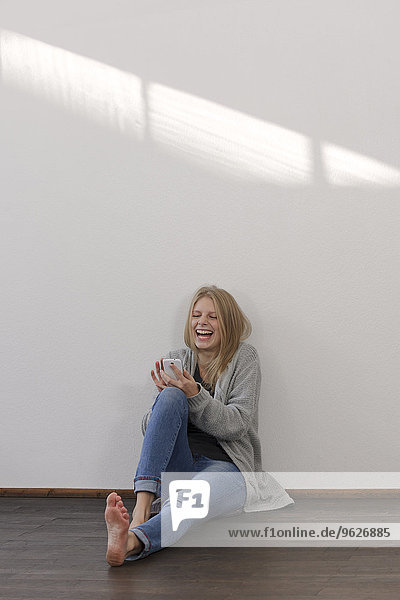 Lachende junge Frau mit Smartphone